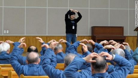 An aerobics instructor leads elderly inmates in simple exercises.
