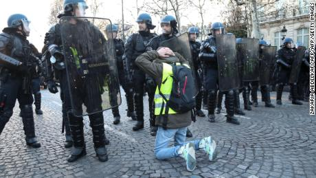 A yellow vest protester kneels in front of police on the Champs-Elysees in Paris on Saturday.