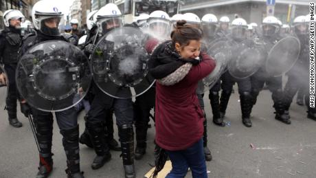 Riot police forces spray tear gas at a woman during copycat protests Saturday in Brussels, Belgium.