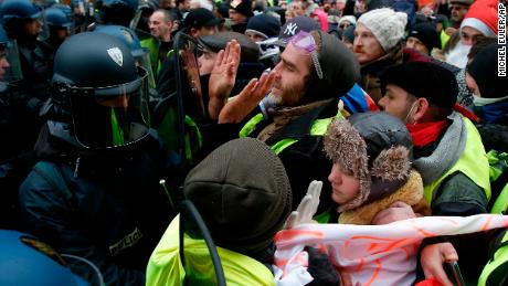 """Yellow vest"" demonstrators face riot police officers Saturday in the French capital."