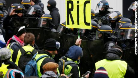 "A Paris protester holds a ""RIC"" sign Saturday in a reference to a demand for a citizens' referendum."