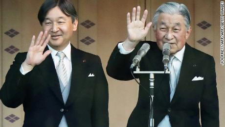 Japan's Emperor Akihito and his son, Crown Prince Naruhito wave to the crowd during the New Year's greeting ceremony at the Imperial Palace in Tokyo on January 2, 2019.