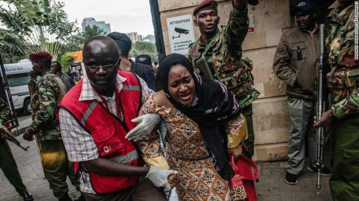 A woman is escorted from the Riverside Drive complex in Nairobi.