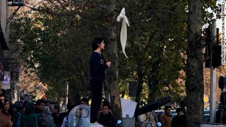 Vida Movahedi stands on a telecoms box on a Tehran street after removing her headscarf and holding a stick to protest against the country's compulsory hijab rules.