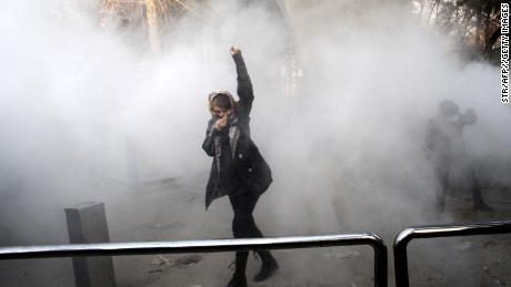 An Iranian woman raises her fist amid the smoke of tear gas at the University of Tehran in December 2017.