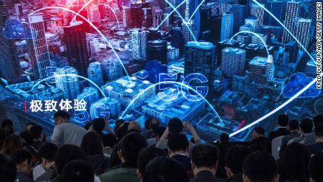 Journalists watch a trailer during a press conference about new 5G Huawei products.
