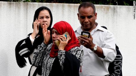 Des personnes attendent vendredi devant une mosquée du centre de Christchurch, en Nouvelle-Zélande.