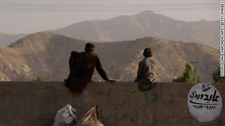 """A pair of young Afghans sit on a wall as they watch a game on the outskirts of Kabul. """"When I started filming them, they didn't have a grass pitch in the whole country. A lot of the guys had never played with a leather ball,"""" Albone reflects."""