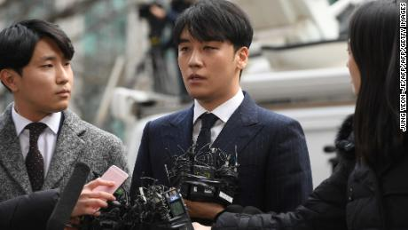 Seungri (center), a member of the K-Pop boy group BIGBANG, speaks to the media as he arrives for questioning over criminal allegations at the Seoul Metropolitan Police Agency in Seoul on March 14, 2019.