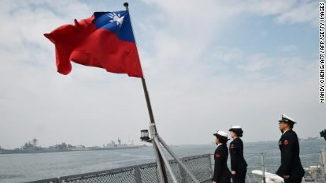 Taiwanese sailors salute the island's flag on the deck of the Panshih supply ship after taking part in live fire drills, at the Tsoying naval base in Kaohsiung on January 31, 2018.