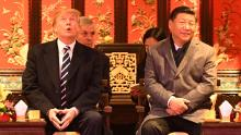 US President Donald Trump  looks up as he sits beside China's President Xi Jinping during a tour of the Forbidden City in Beijing on November 8, 2017.