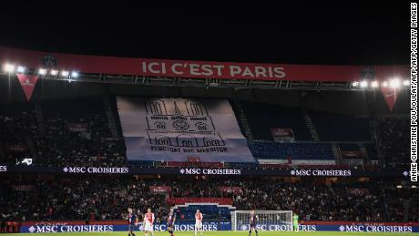 """PSG fans hold aloft a banner showing a drawing of Notre-Dame with the Paris city motto: """"Fluctuat Nec Mergitur"""" (""""She is tossed but not sunk"""")"""