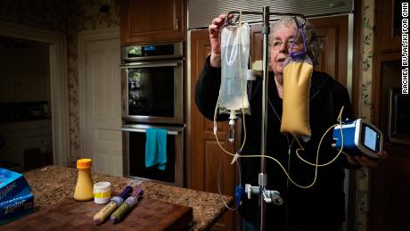Dafoe prepares an IV bag and feeding tubes in their home's kitchen.