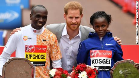 Prince Harry poses with the winners of the men's and women's race after presenting them with their medals.