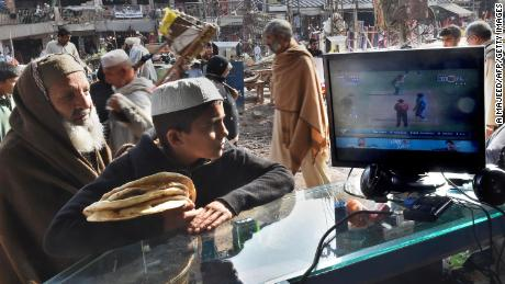 Afghan refugees watch the live broadcast of the Cricket World Cup match between Afghanistan and Bangladesh at a market in Peshawar in February 2015.