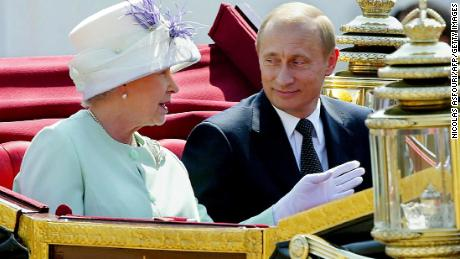 Putin and the Queen share an open carriage along the Mall following his arrival in London in 2003.