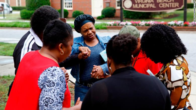 Members of Mount Olive Baptist Church pray near a municipal building in Virginia Beach.
