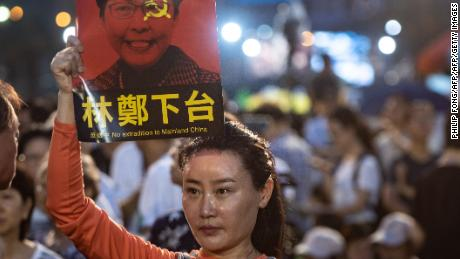 A woman holds a poster of Hong Kong Chief Executive Carrie Lam, against a proposed extradition law, before a candlelight vigil at Victoria Park in Hong Kong on June 4, 2019.