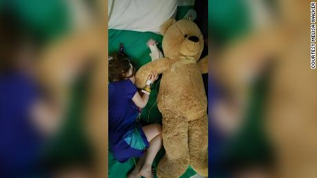 Alex Walker, 4, cuddles a teddy bear in the hospital.