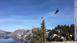 A helicopter flies over Crater Lake.