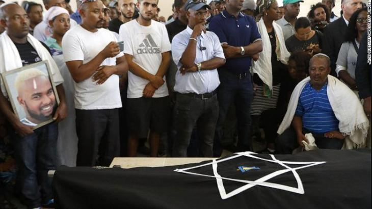 Worka (R), the father of Solomon Teka, mourns over his body during his funeral.