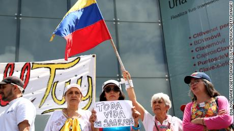 """Venezuelans wave flags and hold signs at a demonstration called by opposition leader Juan Guaidó. The motto of the protest is """"No more torture."""""""