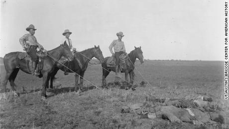 Texas Rangers pose on October 8, 1915, while holding ropes tied to corpses.
