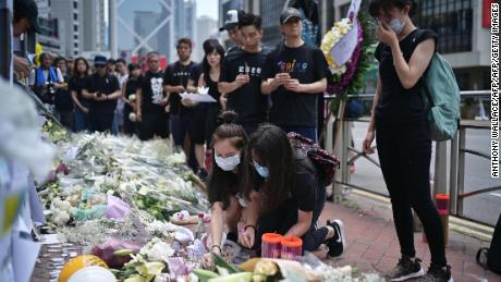 Mourners in Hong Kong place flowers and offer prayers on June 16, 2019, at the site where a protester died.