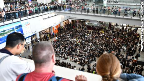 Tourists watch as protesters gather in the arrivals hall of Hong Kong international airport on July 26.