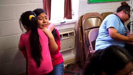 Edna Perez, 14, hugs one of her sisters inside the Trinity Mission Center in Forest, Mississippi. Their father was detained and is still in custody.