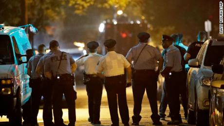 Police officers watch as a gunman is apprehended following a standoff Wednesday night.