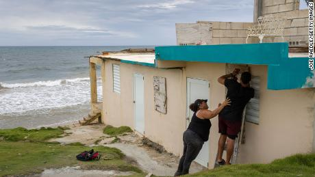Ya Mary Morales (L) and Henry Sustache put plywood over the windows of their home as they prepare for the arrival of Tropical Storm Dorian.