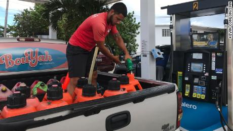 Mathew Cabral fills gas cans before the storm.