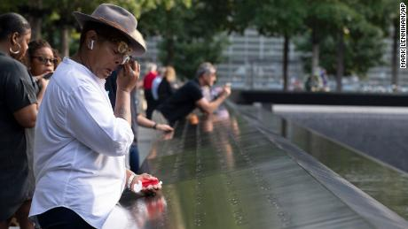 A woman wipes away tears as she stands next to the north pool prior to a ceremony marking the 18th anniversary of the attacks of September 11, 2001, at the National September 11 Memorial.