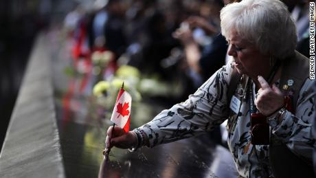 Vernoy Paolini places a Canadian flag in the name of a Canadian victim of the September 11 terrorist attacks at the National September 11 Memorial on Wednesday.
