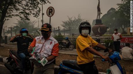 Motorcyclists wear protective masks in Palangkaraya city in Central Kalimantan.