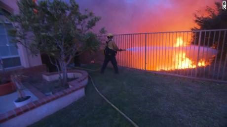 A firefighter sprays water in the form of flames to a house in Los Angeles. Porter Ranch area Friday morning.