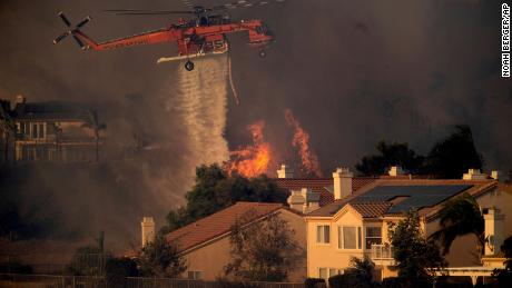 A helicopter dropped water while it was fighting the Saddleridge fire in northeastern Los Angeles on Friday.