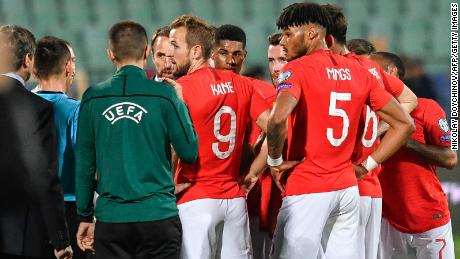 England's players speak with  officials during a temporary interruption due to racist abuse.