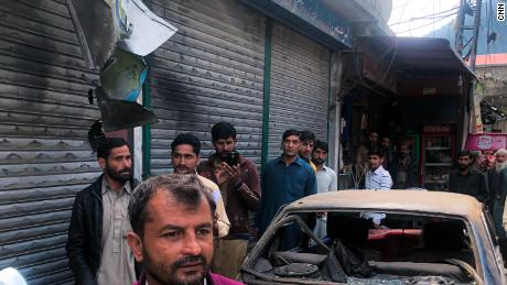 Scorched shutters, ripped store boards and a destroyed car on the main street of Jura in Pakistani-administered Kashmir on October 22, 2019.
