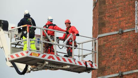 Members of Lancashire Fire and Rescue Service use a hydraulic platform at Dixon's Chimney in Carlisle, England, where a man was hanging upside down from the top of the 270-foot chimney.