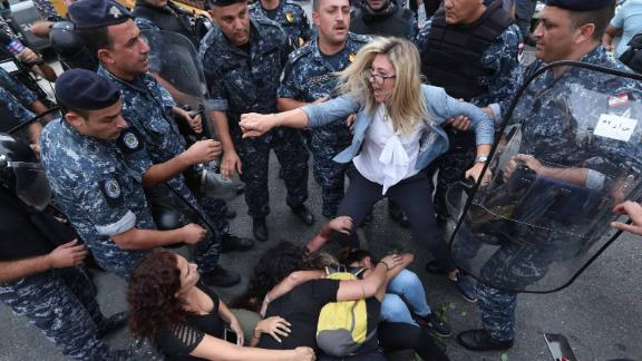 A Lebanese demonstrator scuffles with security forces trying to disperse protesters who were blocking a major bridge in Beirut on Sunday, October 27.