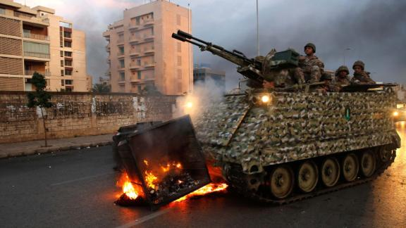 An armored personnel carrier removes a burning garbage container set alight by anti-government protesters on Monday, October 28.