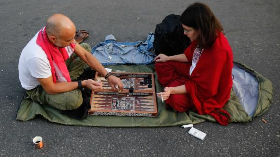 Anti-government protesters play a dice game as they block a main highway during during demonstrations.