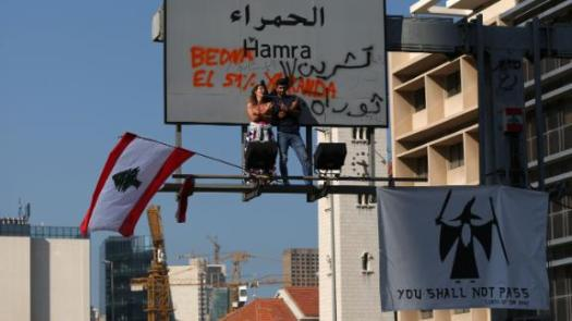 Protesters perch on an overhead road sign in Beirut on November 4.
