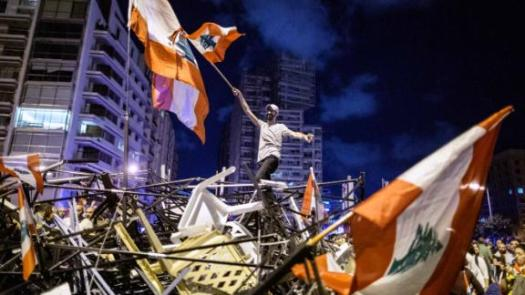 An anti-government protester waves a Lebanese flag as he stands on top of a pile of broken tents in Martyrs' Square on October 29.