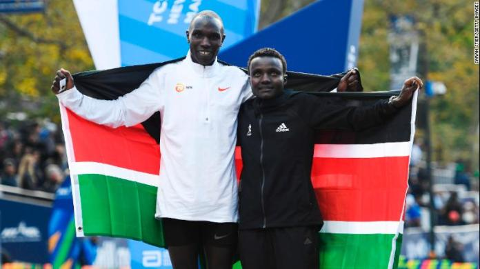 Geoffrey Kamworor and Joyciline Jepkosgei pose with the Kenyan flag after the New York Marathon.