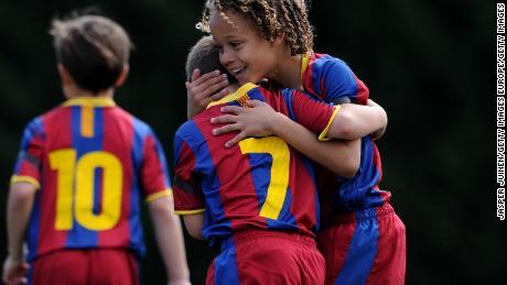 Un bambino di otto-anno-vecchio Xavi Simons (a destra) festeggia un gol con un compagno di squadra durante il 2011, match per il FC Barcelona's team giovanile.