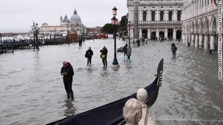 Persone a piedi passato un filamento gondola tutta allagata Riva degli Schiavoni argine San Marco's Square in background.