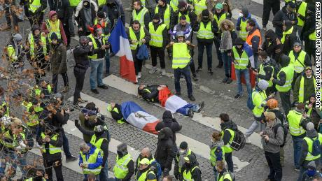 Protesters wrapped in French flags lie on the ground near riot police on the Champs Elysees on December 8, 2018.